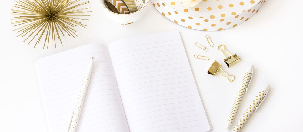 gold office stationary and notepad on white desk